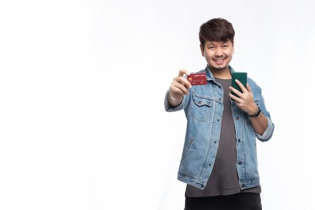 Homem asiático com uma carinha sorridente segurando um cartão de crédito e um smartphone