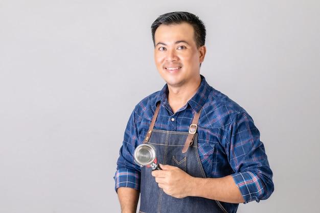Homem asiático com uniforme de barista segurando uma máquina de café