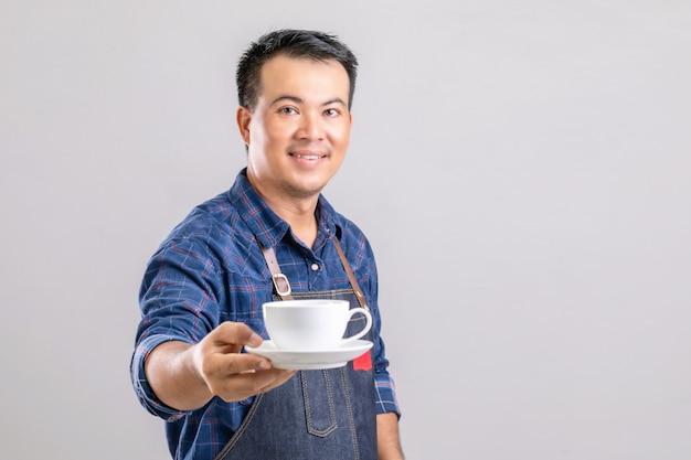 Homem asiático com uniforme de barista segurando uma xícara de café