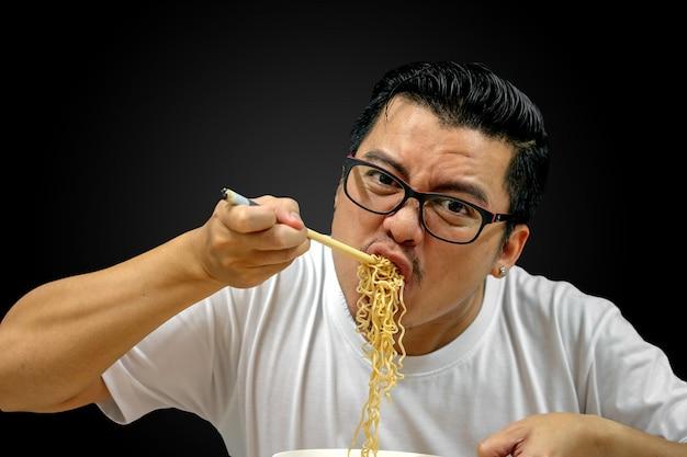 Homem asiático comendo macarrão instantâneo isolado no preto, com traçado de recorte