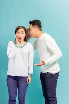 Homem asiático compartilhando segredos ou sussurrando fofocas no ouvido da namorada, estúdio azul
