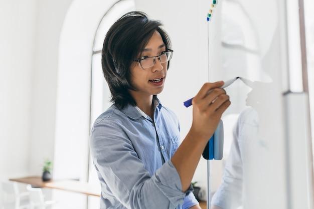 Homem asiático concentrado em camisa azul usando flipchart e marcador para o trabalho