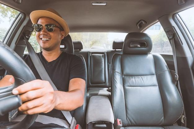 Homem asiático considerável novo que conduz o carro para viajar.
