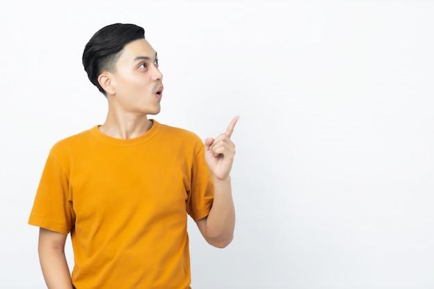 Homem asiático considerável novo que está sendo surpreendido com seu dedo que aponta até o copyspace no fundo branco.