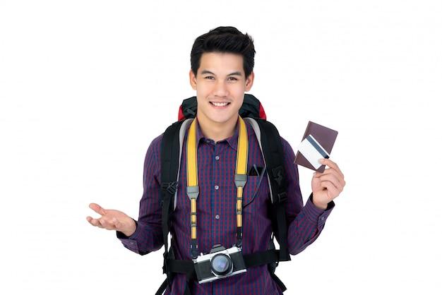 Homem asiático considerável novo que guarda o passaporte e o cartão de crédito apreciado tendo feriados