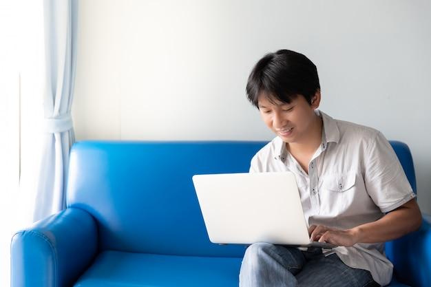 Homem asiático considerável que usa o portátil para trabalhos e atividades em linha ao sentar-se no sofá azul na manhã