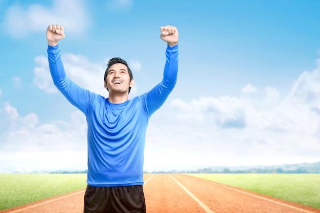 Homem asiático corredor com expressão animada depois de uma corrida na pista de corrida