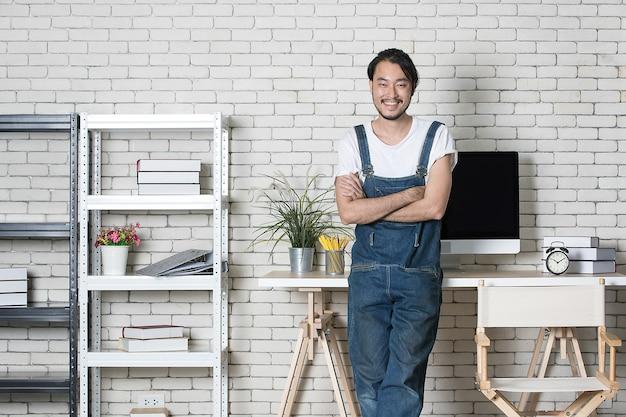 Homem asiático de barba jovem hippie em pé com feliz em seu novo escritório moderno mínimo de inicialização, conceito de empresário feliz com a partida de pequenos negócios.