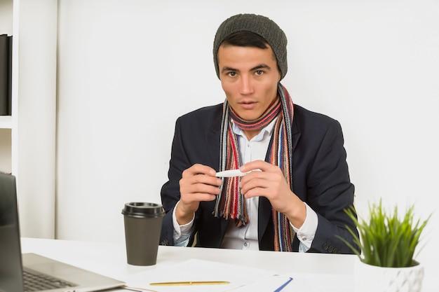 Homem asiático de chapéu, cachecol e jaqueta mede a temperatura com um termômetro no escritório desde que rompido o aquecimento ou resfriamento do ar condicionado em excesso. exacerbação de resfriados e vírus do outono