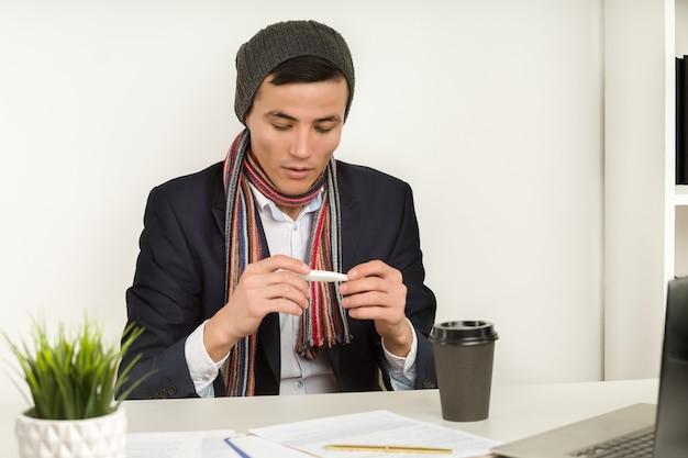 Homem asiático de chapéu, cachecol e jaqueta mede a temperatura com um termômetro no escritório.