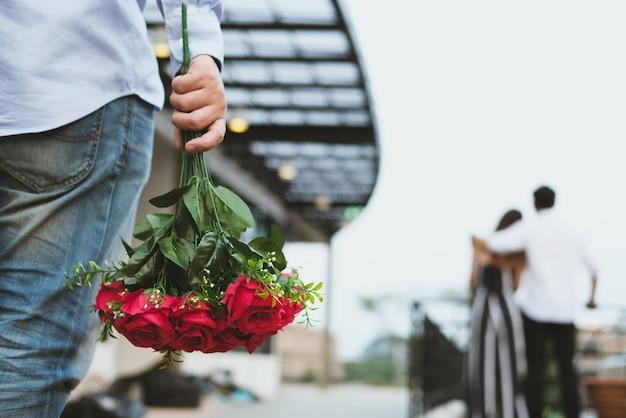 Homem asiático de coração partido segurando um buquê de rosas vermelhas, sentindo-se triste ao ver uma mulher namorando com outro homem.