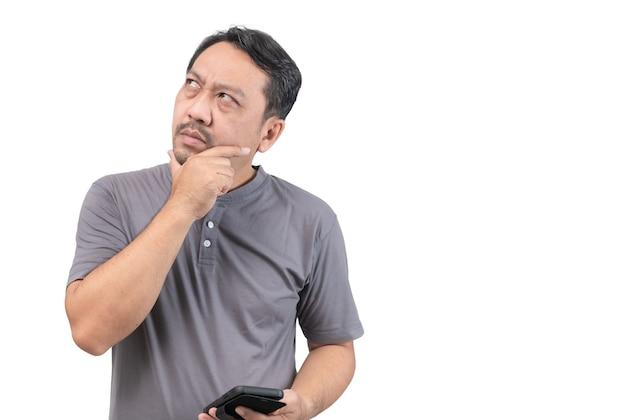 Homem asiático de meia-idade segurando um telefone inteligente e pensando isolado no fundo branco, copie o espaço