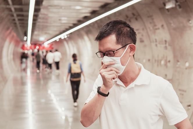 Homem asiático de meia idade usando óculos e máscara facial médica, espirros e tosse, surto de coronavírus wuhan, poluição do ar e conceito de saúde