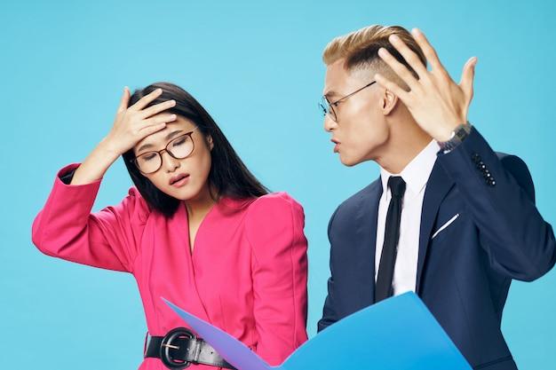 Homem asiático de negócios e mulher olhando documentos corporativos