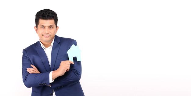 Homem asiático de negócios segurando papel em formato de casa apresentando isolado no branco