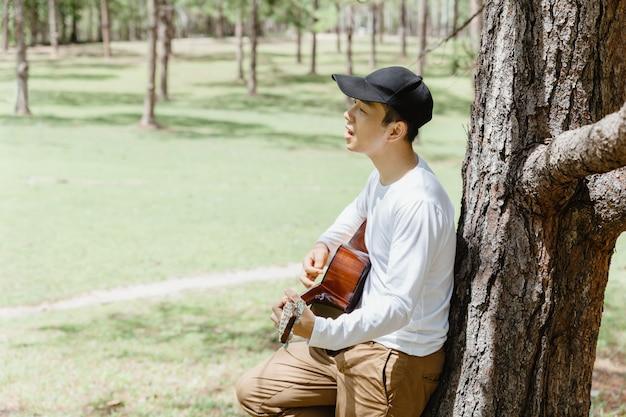 Homem asiático de pé e cantando com guitarra debaixo de pinheiro.