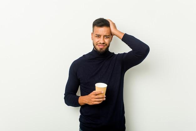 Homem asiático de raça mista jovem segurando um café para viagem sendo chocado, ela se lembrou de uma reunião importante.