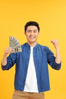 Homem asiático de sucesso. jovem feliz segurando dinheiro em pé e com os braços erguidos, isolado no fundo amarelo