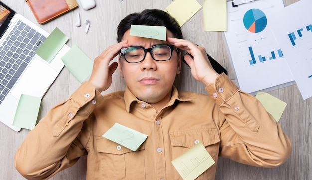 Homem asiático deitado em uma pilha de papéis e cansado do trabalho