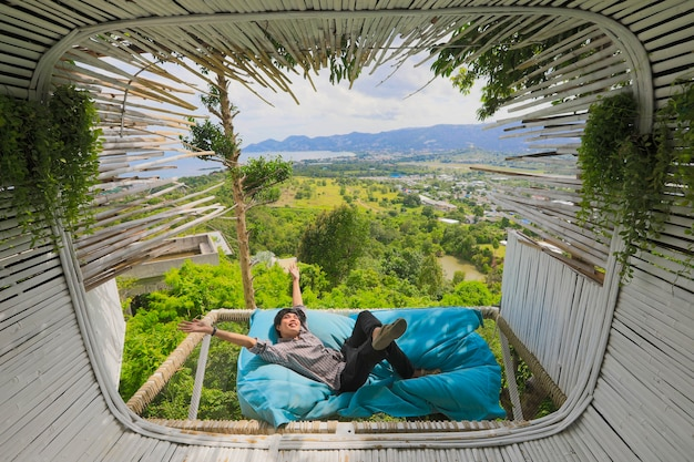 Homem asiático deitado no sofá-cama homem turista asiático está deitado no sofá-cama perto do terraço no café ao ar livre com vista panorâmica sobre as montanhas. hora de relaxar