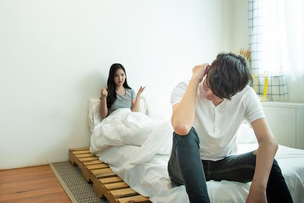 Homem asiático deprime e mulher com relacionamento infeliz sentar na cama depois de ter uma discussão, problema social em casal vive.