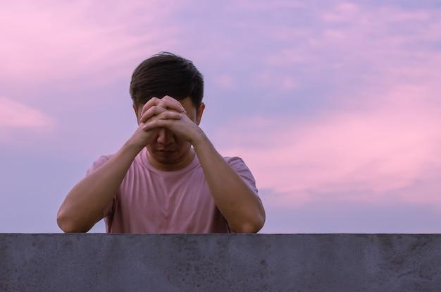 Homem asiático deprimido e miserável fica sozinho com o fundo do céu