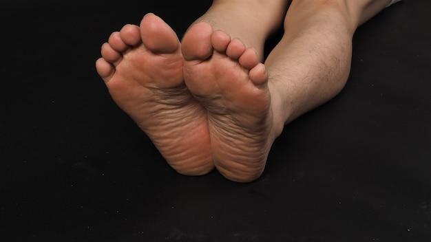 Homem asiático descalço e sola dos pés é isolado no fundo preto.