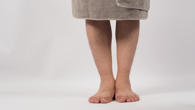 Homem asiático descalço está de pé e as pernas enroladas em uma toalha de banho cinza, isolada no fundo branco.