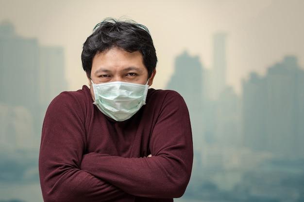 Homem asiático, desgastar, a, máscara face, contra, poluição ar, com, gelado, em, a, sacada, de, apartamento alto