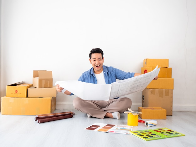 Homem asiático design e pensando para decorar a casa