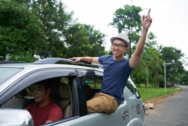 Homem asiático, dirigindo o carro e alegre amigo sentado na janela da porta traseira