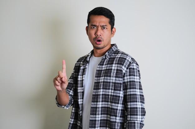 Homem asiático diz não e faz gesto de sinal com o dedo