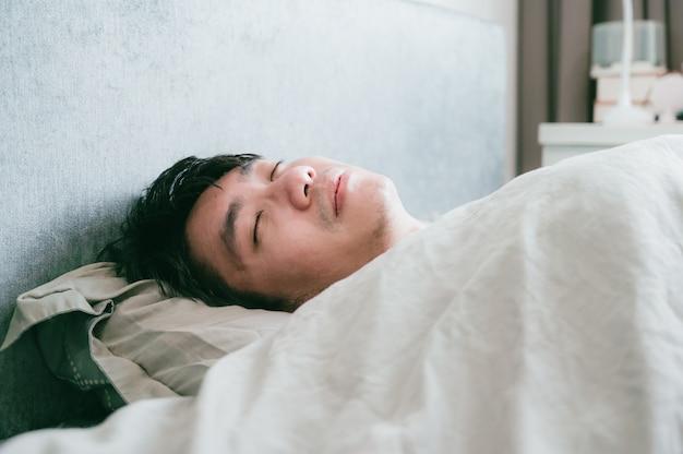 Homem asiático doente dorme na cama. homem paciente descansando da doença.