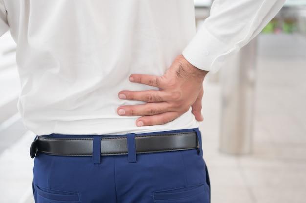 Homem asiático doente e doente, sofrendo de dores nas costas, problemas na coluna, herniação de disco, luxação ou deslocamento do disco espinhal, síndrome do consultório