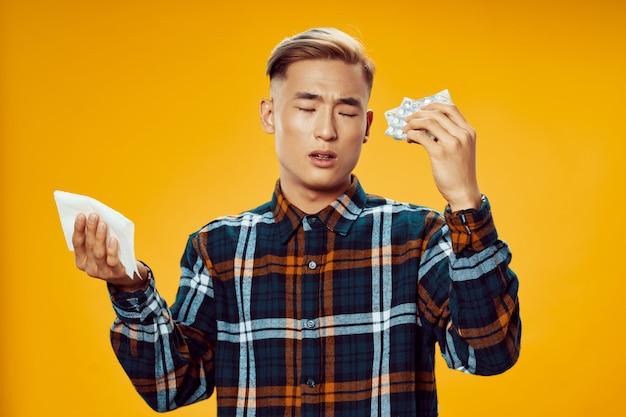 Homem asiático doente segurando comprimidos