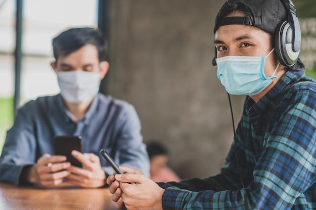Homem asiático, dois, pessoas, uso, máscara facial, sentando, em, café, estilo vida, novo, normal, social, distanciamento, após, bloquear, corona, vírus