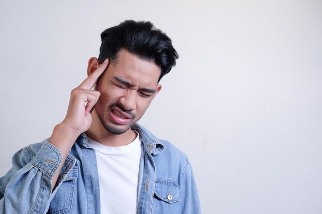 Homem asiático é dor de cabeça, sentir-se doente com cara dolorosa e tocar sua cabeça em branco