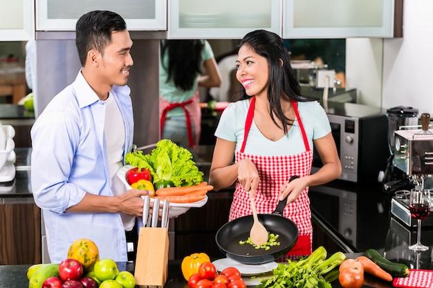 Homem asiático e mulher cozinhando juntos