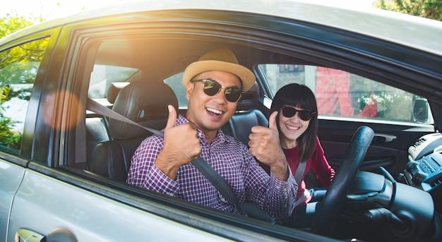 Homem asiático e mulher dos pares felizes do momento que sentam-se no carro. aproveitando o conceito de viagens.