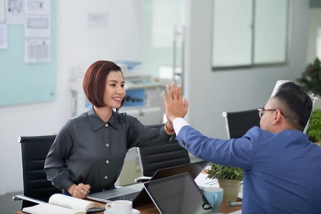 Homem asiático e mulher em trajes profissionais, sentado à mesa na sala de reuniões e fazendo mais cinco