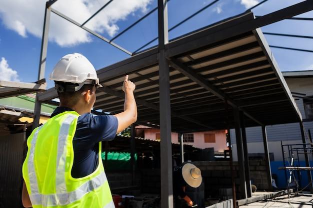 Homem asiático e mulher engenheiro civil papel plano edifício arquiteto usando capacete de segurança branco olhar para o local de construção.
