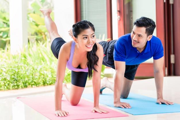 Homem asiático e mulher no exercício da aptidão em casa