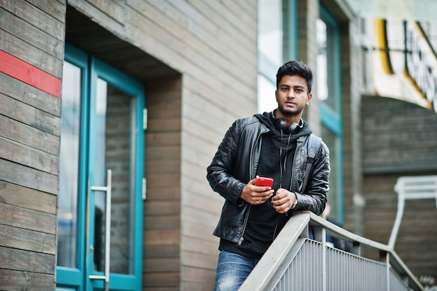 Homem asiático elegante e casual na jaqueta de couro preta, fones de ouvido com celular vermelho nas mãos colocadas na rua