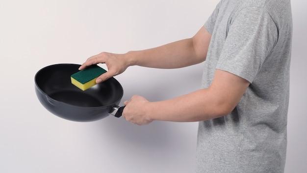 Homem asiático em camiseta cinza limpando a frigideira antiaderente com a prática esponja de lavar louça amarela no lado macio e verde no lado duro para higiene após cozinhar