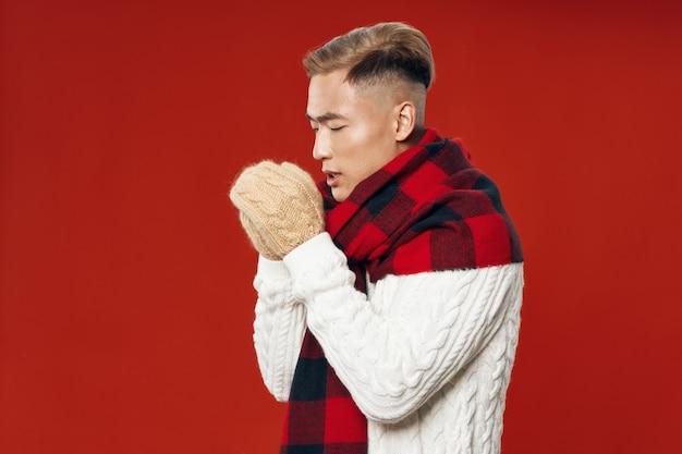 Homem asiático em roupas de inverno quente, posando em um espaço colorido espaço