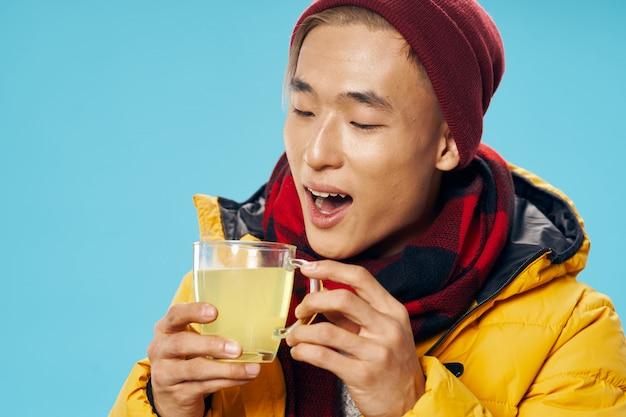 Homem asiático em roupas de inverno quente posando no estúdio em uma superfície colorida