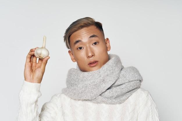 Homem asiático em roupas de inverno quente, segurando um alho