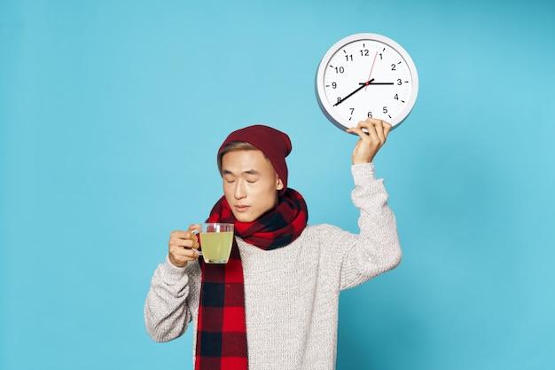 Homem asiático em roupas de inverno quente, segurando um relógio