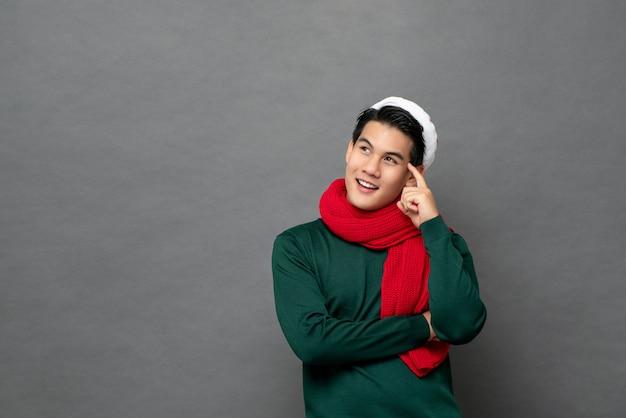 Homem asiático em roupas de tema de natal pensando e olhando para o espaço de lado