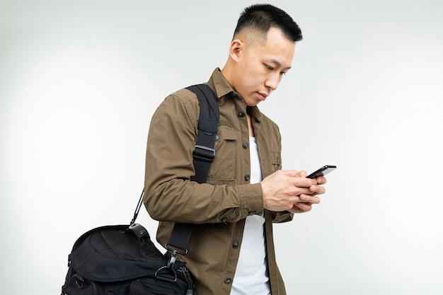 Homem asiático em roupas urbanas com uma bolsa com um telefone vrukh vai sobre um fundo branco